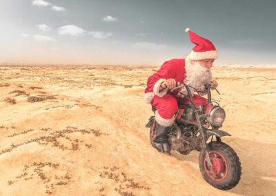 Mainoskuva, jossa joulupukki ajaa mopolla hiekka-aavikolla.