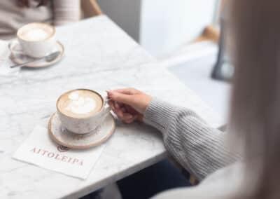 Yrityskuvassa kahvikuppi, jota nainen pitelee korvasta kiinni kahvilassa.