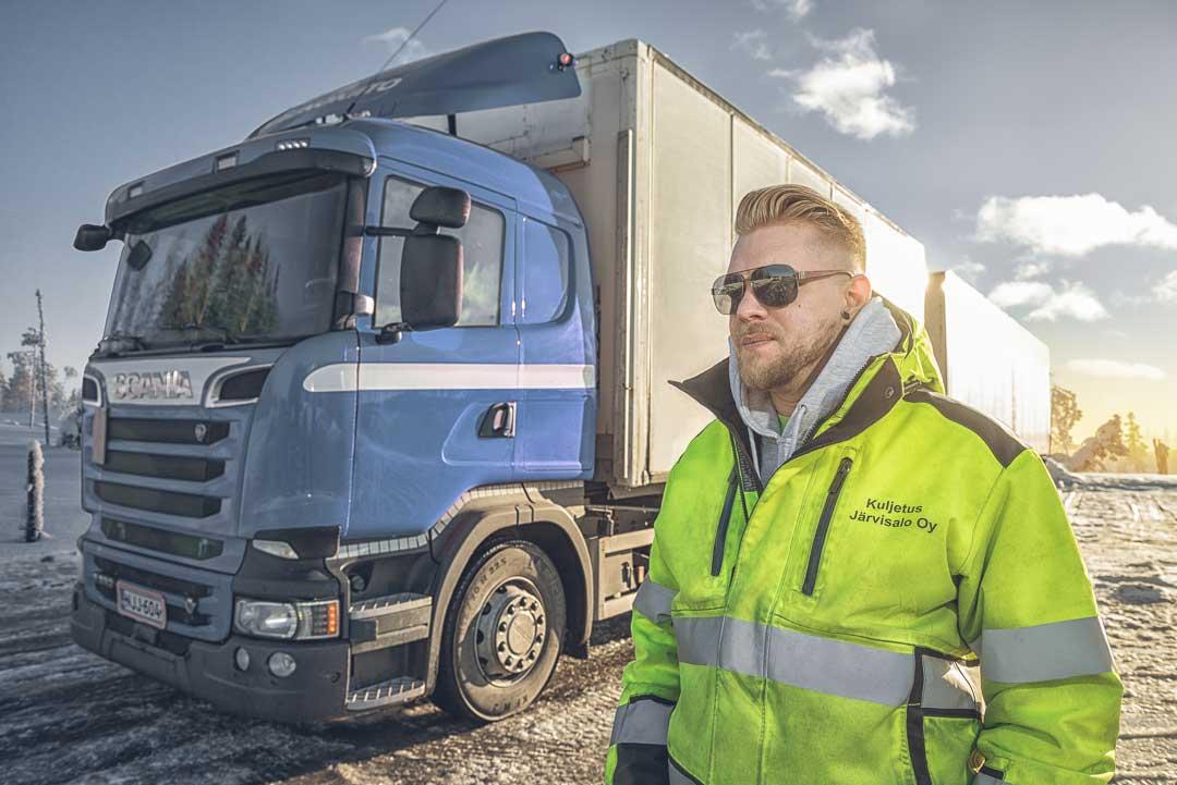 Kuljetusliikkeen mainoskuva - rekka-auton kuljettaja seisoo rekka-auton vieressä aurinkolasit päässä talvisessa maisemassa.