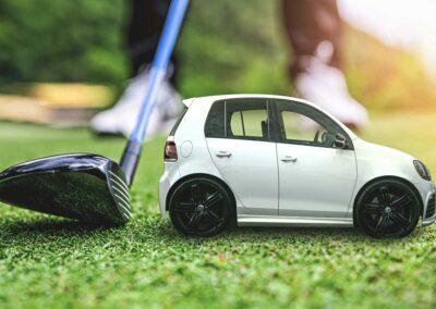 Mainoskuva, jossa miniatyyriauto golfradalla vieressään golfmaila.