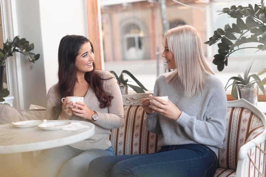 Mainoskuva, jossa kaksi naista istuu kahvilassa ja pitelee kahvikuppeja käsissään.