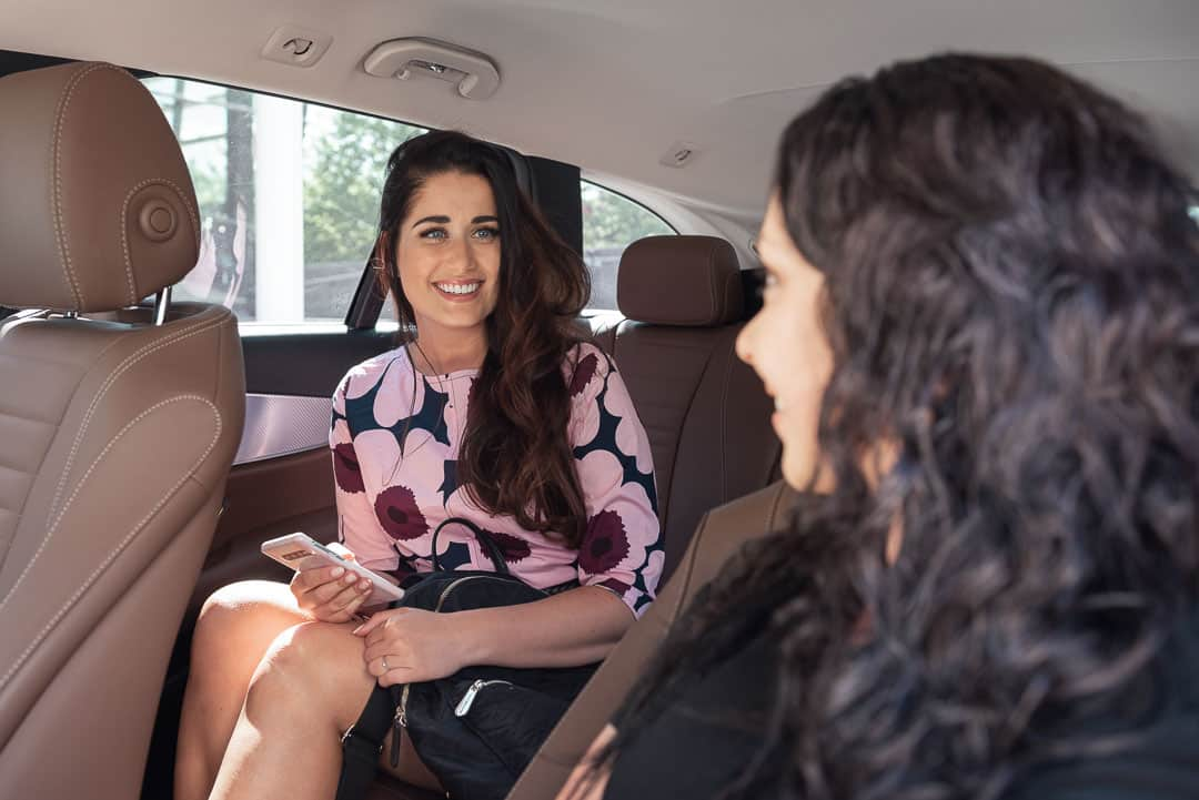 Nainen istuu taksin kyydissä takapenkillä ja taksinkuljettaja katsoo naista.