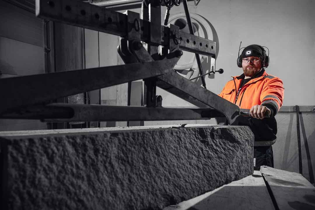 Työntekijä siirtää painavaa kiveä nosturilla tehdashallissa.