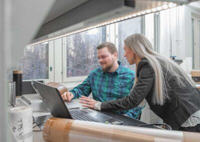 Kaksi työntekijää laboratoriossa tekee työtä tietokoneen ääressä.