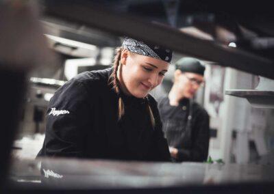 Keittiötyöntekijä tekee työtään ravintolan keittiössä.