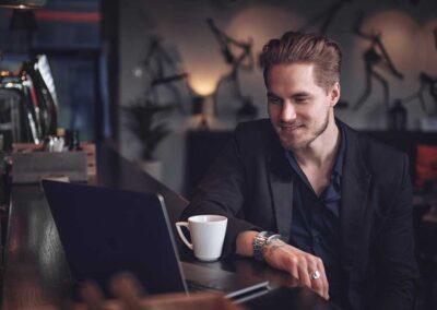 Mies kahvilla ravintolassa, katsoo tietokonetta baaritiskillä.