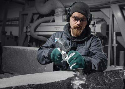 Työntekijä muotoilee kiveä taltan ja vasaran avulla.