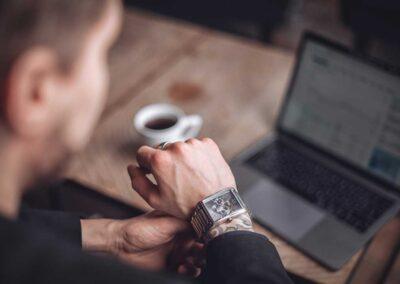Mainoskuva, jossa mies istuu kahvilla tietokone pöydällä ja kello kädessä.