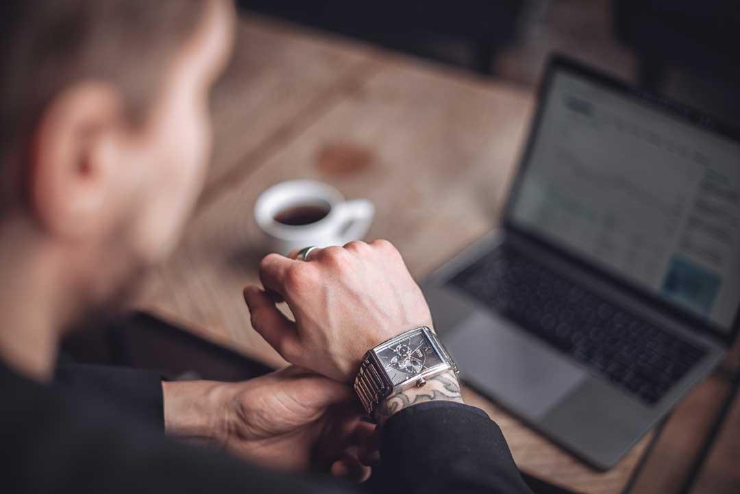 Mies istuu kahvilla tietokone pöydällä ja kello kädessä.
