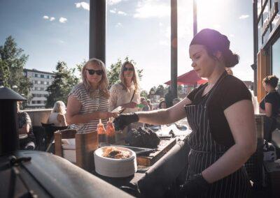 Ravintolatyöntekijä palvelee kahta asiakasta ravintolan terassilla.