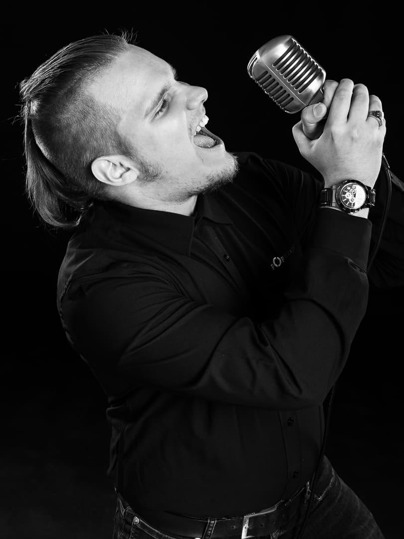Henkilöstökuva, missä mies laulaa mikrofoniin.
